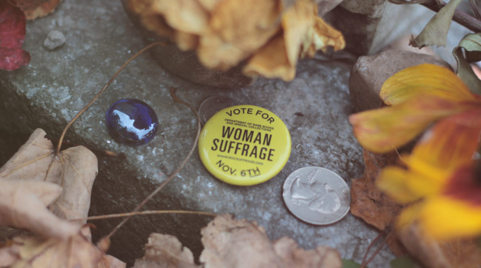 A marble, quarter, and woman suffrage pin left at Susan B. Anthony's gravesite by visitors.