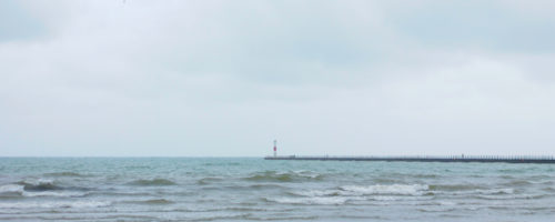 A lighthouse at the end of a long pier at Lake Ontario Park.